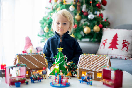 Cute blond child, toddler boy with gingerbread houses, made by kids, decorated with toys, trees and playground on a table