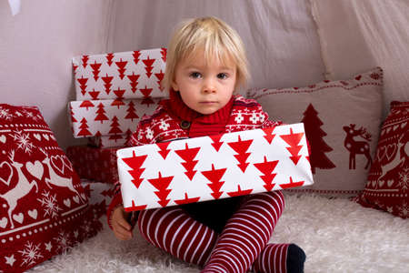 Cute little blonde boy with Christmas sweater, opening presents at home on Christmas