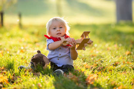 Beautiful blonde two years old toddler boy, playing with wooden plane and teddy bear in the park on sunset, sunny autumn day
