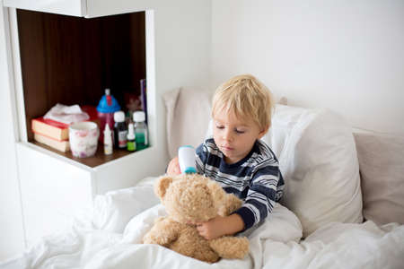 Little toddler blond child, playing with teddy bear in bed, while being sick, checking his temperature with digital thermometer