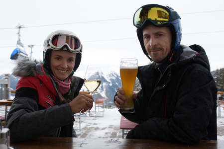 Woman and man, husband and wife, drinking beer and wine in a restaurant on a ski slope during ski break in the afternoon on a cloudy day