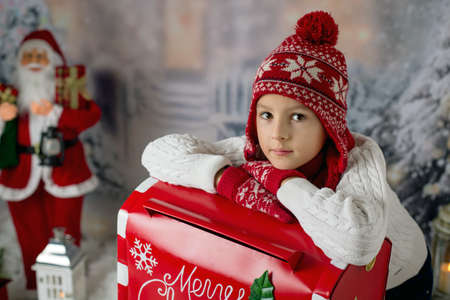 Little child, boy, sending letter to santa in christmas mailbox, christmas decoration around him, outdoor snow shot