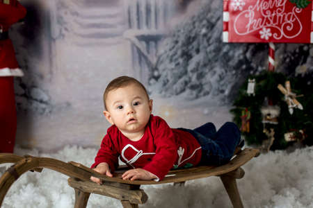 Sweet little baby boy with christmas decorations, playing in the snow Stock Photo