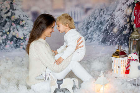 Mother and toddler child, blond boy, playing together in the snow with wooden toy horse