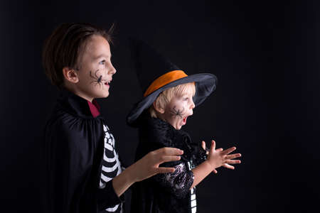 Children. brothers, dressed for Halloween, playing at home, isolated image on black
