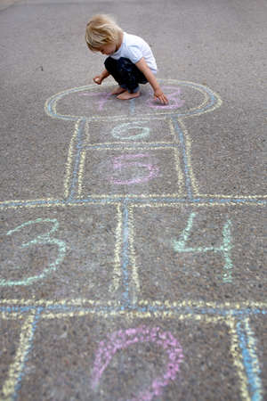 Child, blond boy, playing hopscotch on the street, summertime