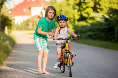 Older brother, helping his little brother to learn how to ride a bike, holding him and teaching him biking Foto de archivo