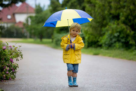 Mother and toddler child, boy, playing in the rain, wearing boots and raincoats