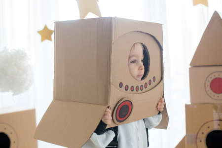 Sweet toddler boy, dressed as an astronaut, playing at home with cardboard rocket and handmade helmet from box