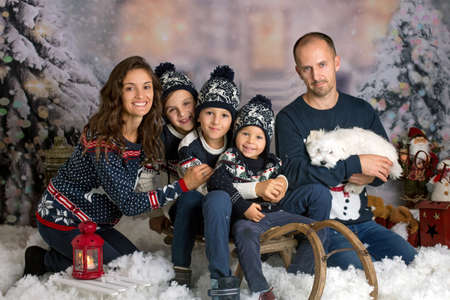 Happy family, parents with three children and puppy dog, having christmas pictures taken in the snow