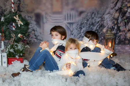 Children, sitting in the snow, wrapped in toilet paper and christmas light strings, looking at camera Stock Photo