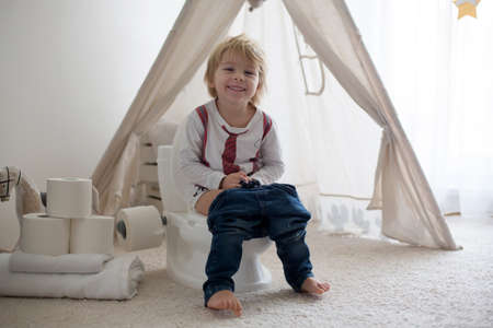 Cute toddler child, boy, sitting on a baby toilet potty, playing with toys