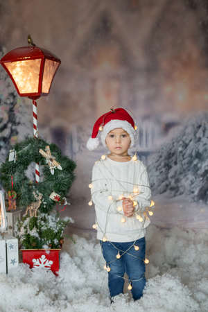 Cute toddler boy, blond child, standing in front of the house, wrapped in christmas string lights, feeling trapped