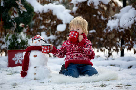 Sweet blond toddler child, boy, playing in garden with snow, making snowman, happy kid winter time outdoors