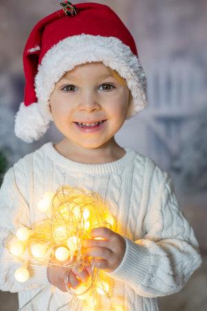 Beautiful toddler boy, holding christmas light string, looking at camera, close christmas portrait 版權商用圖片