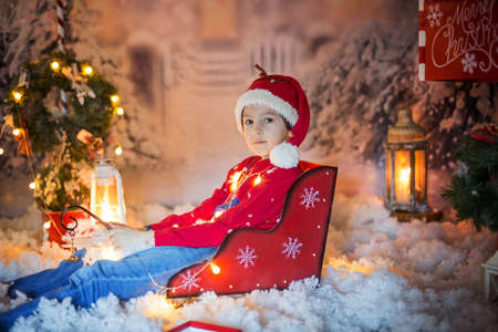 Cute child, school boy, opening present for christmas, decoration around him, outdoor shot, outdoor snow shot