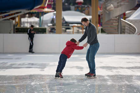 Happy excited little boy and his young father learning ice-skating outdoor
