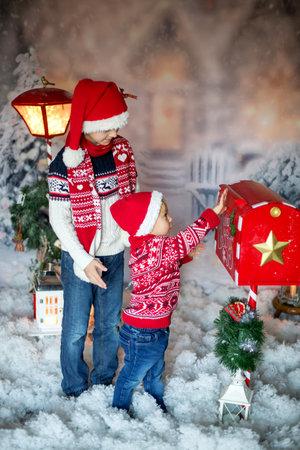 Cute children, school boy and toddler, sending letter to santa in christmas mailbox, christmas decoration around him, outdoor shot, outdoor snow shot 版權商用圖片