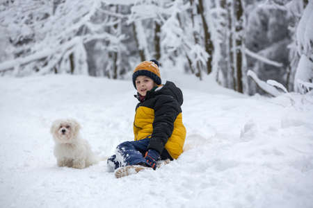 Sweet happy child with white puppy dog, playing in deep snow in forest