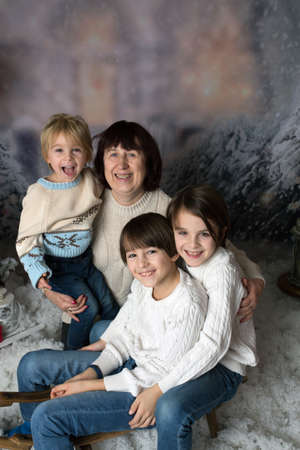 Grandmother and three grandchildren, boys, having Christmas portrait taken in the snow, studio shot with sledge