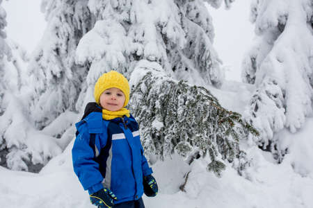 Sweet happy child, playing in deep snow in forest