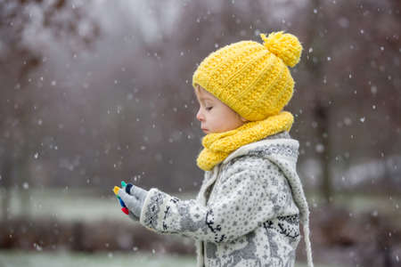 Beautiful blond toddler child, boy, with handmade knitted sweater playing in the park with first snow, enjoying