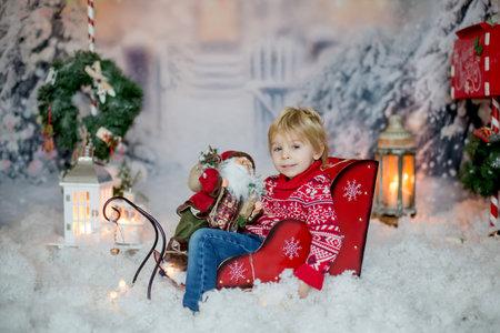 Cute little toddler blond child, boy, sitting in sledge outdoors, snowy winter scene, christmas decoration around him