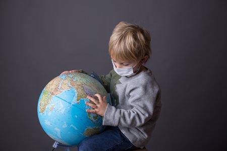 Cute toddler child, boy, hugging big globe, wearing mask, Covid 19 travel restrictions. Isolated image 版權商用圖片