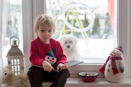 Cute blond toddler child, sitting on the window, looking at the snow falling outside, reading a book