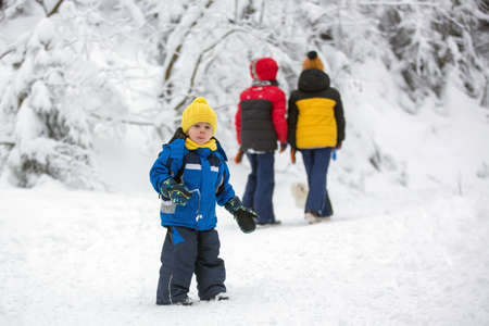 Sweet happy children, brothers, playing in deep snow in forest, frosted trees and beautiful landscape 版權商用圖片