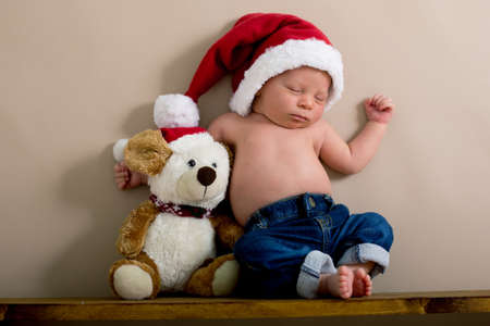 Newborn baby boy wearing a christmas hat and jeans, sleeping on a shelf next to Teddy Bears. Shot in the studio on a creamy background, shot from above