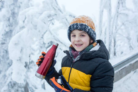 Sweet happy child, drinking hot tea while hiking, playing in deep snow in forest, frosty cloudy day 版權商用圖片