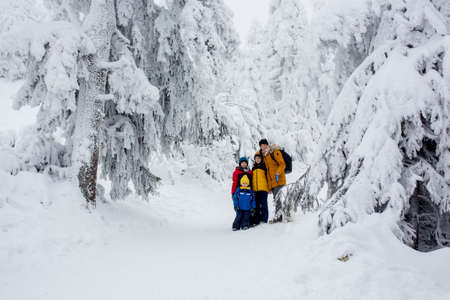 Happy family with three children and puppy dog, hiking in mountains wintertime, lots of snow, beautiful winter forest