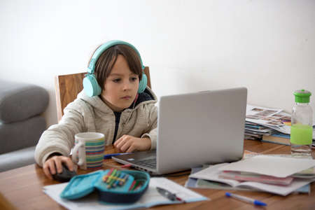 School child, sitting at the table with laptop, writing school tasks while homeschooling, pandemic dintance teaching environment