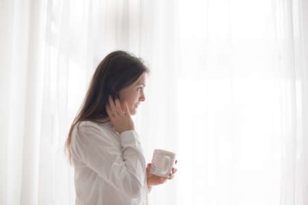 Middle age woman with white dress, drinking coffee at home, looking out of the window, white background
