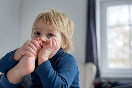 Cute blond toddler child, sucking his foot thumb, making funny faces, laughing Stock Photo