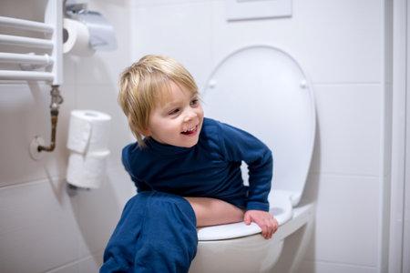 Cute toddler boy, sitting on toilet, smiling