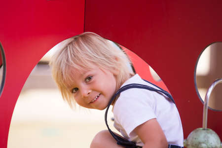 Sweet toddler child, boy, playing on the playground summertime