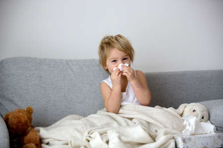 Blond toddler child, wiping his nose in a tissue, sneezing and coughing at home on a sofa
