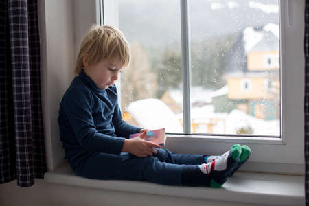 Toddler child, sitting on the window, watching the snow falling, reading little book