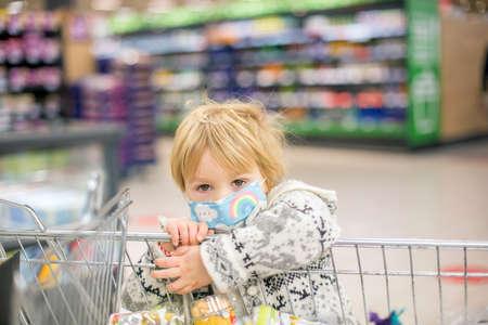 Cute toddler child, boy, wearing medical mask in supermarket store during pandemic lockdown