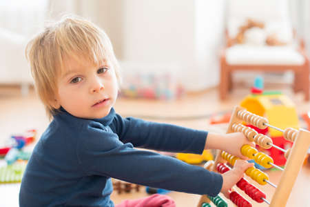 Sweet blond preschool child, toddler boy, playing with abacus at home, construction on the floor behing him