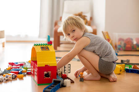 Cute child, playing with colorful toy blocks. Little boy building house of block toys sitting on the floor in sunny spacious bedroom. Educational game for toddlers