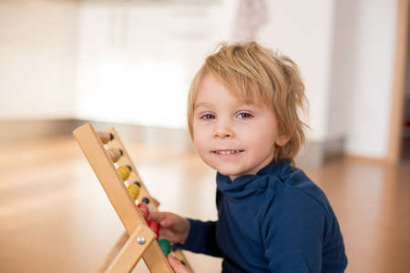 Sweet blond preschool child, toddler boy, playing with abacus at home,construction on the floor behing him