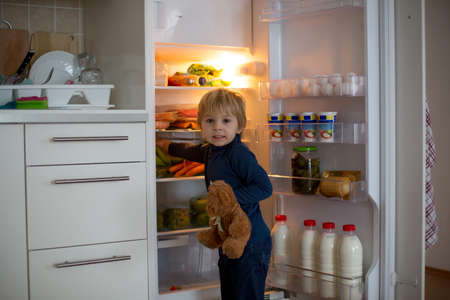 Cute toddler blond child, opening the fridge door and taking fruits adn vegetables and healthy food from the refrigerator