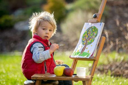 Sweet toddler child, painting eggs in garden with little chicks running around him on sunset