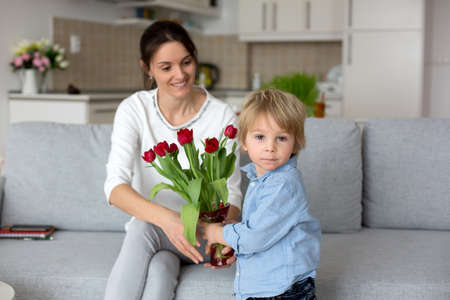 Child, toddler boym holding flowers for mother for her holiday, mothers day, red tulips in a beautiful vase