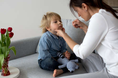 Mother, testing her child for covid at home, making home allowed swab tests to prove negative result