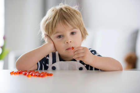 Cute little child, toddler boy, eating alfa omega 3 child suplement vitamin pills at home for better imunity Фото со стока