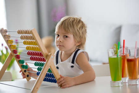 Sweet toddler child, blond boy, learning math at home with colorful abacus, drinking freshly made juice